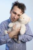 Junger Mann mit einem Teddybären Stockbild