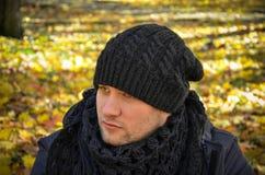 Junger Mann mit einem traurigen Blick mit Herbstblättern Stockfotos