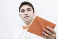 Junger Mann mit einem Umschlag in seiner Hand Stockbild