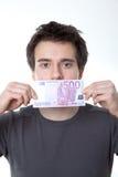 Junger Mann mit einer Banknote auf seinem Mund Stockbilder