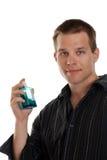Junger Mann mit einer blauen Cologneflasche lizenzfreie stockbilder