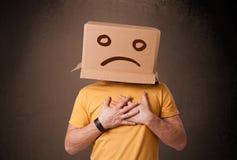 Junger Mann mit einer braunen Pappschachtel auf seinem Kopf mit traurigem Gesicht Lizenzfreies Stockfoto