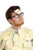 Junger Mann mit einer klebrigen Anmerkung über sein Gesicht, abgedeckt mit gelben Aufklebern stockbild