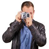 Junger Mann mit einer Lederjacke, die eine Weinlesekamera hält und auf die Kamera - lokalisiert zeigt Lizenzfreie Stockfotografie
