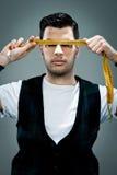 Junger Mann mit einer Meter-Regel vor seinem Gesicht Lizenzfreie Stockfotografie