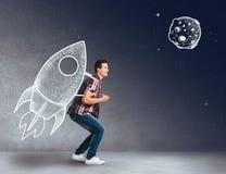Junger Mann mit einer Rakete auf seinem zurück Stockfoto