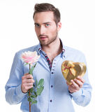 Junger Mann mit einer Rose und einem Geschenk. Lizenzfreie Stockfotos