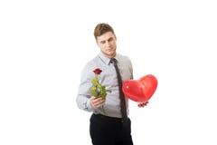 Junger Mann mit einer roten Rose und Herz steigen im Ballon auf Stockfotos