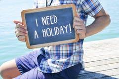Junger Mann mit einer Tafel mit dem Text benötige ich einen Feiertag Stockbild