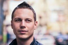 Junger Mann mit einer unscharfen Stadt lizenzfreie stockfotos