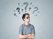 Junger Mann mit geklebtem Auge und Fragezeichensymbolen Lizenzfreie Stockbilder