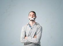 Junger Mann mit geklebtem Mund Stockbilder