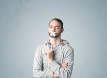 Junger Mann mit geklebtem Mund Stockbild