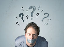 Junger Mann mit geklebtem Mund und Fragezeichensymbolen Stockfoto