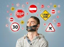 Junger Mann mit geklebtem Mund und Verkehrszeichen Lizenzfreie Stockbilder