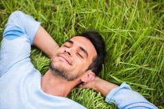 Junger Mann mit geschlossenen Augen, träumend und auf dem grünen Gras sich entspannen lizenzfreie stockfotografie