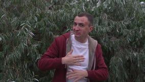 Junger Mann mit Gesicht voll von Lippenstiftkennzeichen von Küssen ist das Tanzen im Freien stock footage