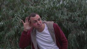Junger Mann mit Gesicht voll von Lippenstiftkennzeichen von Küssen ist setzt seine Hände zum Ohr und zum Hören stock video