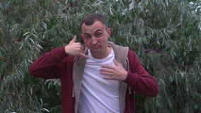Junger Mann mit Gesicht voll von Lippenstiftkennzeichen von Küssen macht anrufen mich Geste stock video