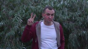 Junger Mann mit Gesicht voll von Lippenstiftkennzeichen von Küssen macht Friedens- und Liebesgeste stock video footage