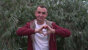 Junger Mann mit Gesicht voll von Lippenstiftkennzeichen von Küssen macht Herzform mit den Händen stock video