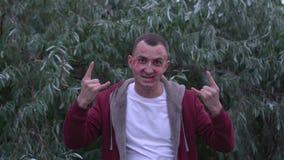 Junger Mann mit Gesicht voll von Lippenstiftkennzeichen von Küssen macht kühle Felsengeste stock video footage
