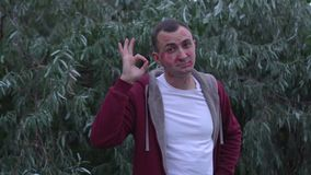 Junger Mann mit Gesicht voll von Lippenstiftkennzeichen von Küssen macht okaygeste stock video