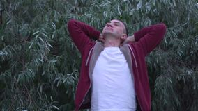 Junger Mann mit Gesicht voll von Lippenstiftkennzeichen von Küssen, Mannstände in entspannter Haltung stock video