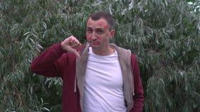 Junger Mann mit Gesicht voll von Lippenstiftkennzeichen von Küssen zeigt Daumen unten stock footage