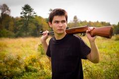 Junger Mann mit Gewehr Stockfotos