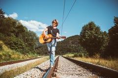 Junger Mann mit Gitarre geht auf Eisenbahnen Stockfotografie