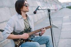Junger Mann mit Gitarre improvisierend bei der Ausführung lizenzfreies stockfoto