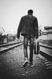 Junger Mann mit Gitarrenkasten in der Hand geht weg. Hintere Ansicht, Schwarzweiss Lizenzfreie Stockfotos