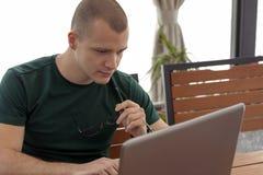 Junger Mann mit Gläsern betrachtet den Laptop und surft das Internet lizenzfreies stockbild