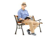Junger Mann mit Gläsern ein Buch auf Holzbank lesend Lizenzfreies Stockfoto