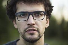 Junger Mann mit Gläsern im Park Stockbild