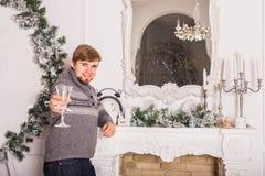 Junger Mann mit Glas Champagner Weihnachts- und des neuen Jahresfeiern Stockfotos