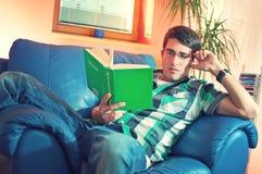Junger Mann mit Glaslesebuch lizenzfreie stockfotos