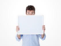 Junger Mann mit halber Gesichtsabdeckung durch ein leeres Brett Lizenzfreies Stockbild