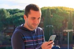 Junger Mann mit Handy auf dem Baumhintergrund, im Freien Stockbild
