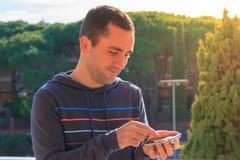 Junger Mann mit Handy auf dem Baumhintergrund, im Freien Stockfotografie