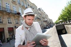 Junger Mann mit Hut unter Verwendung der Tablette in der Stadt Stockfotografie