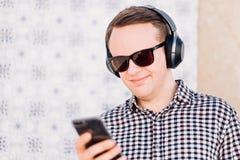 Junger Mann mit Kopfhörern der modernen, guten Qualität schloss an seinen an Lizenzfreie Stockfotos
