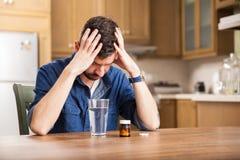 Junger Mann mit Kopfschmerzen Stockfotos