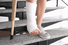 Junger Mann mit Krücke und dem gebrochenen Bein in der Form stockfoto