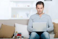 Junger Mann mit Laptop auf Sofa im Raum Lizenzfreie Stockfotos