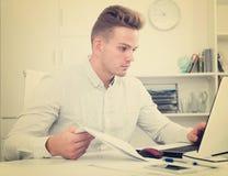 Junger Mann mit Laptop im Büro Lizenzfreies Stockbild