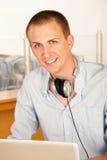 Junger Mann mit Laptop und Kopfhörern Lizenzfreie Stockbilder