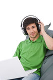 Junger Mann mit Laptop und Kopfhörern Stockbilder