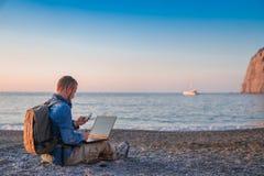Junger Mann mit Laptopfunktion auf dem Strand Freiheit, Fernarbeits-, Freiberufler-, Technologie-, Internet-, Reise- und Ferienko stockfotos